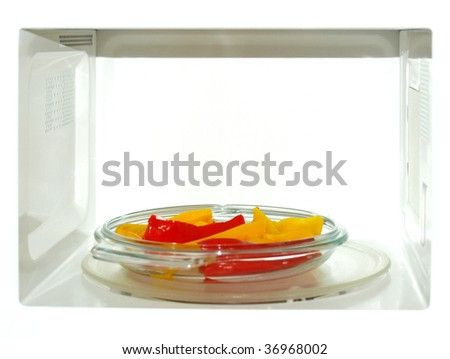 Microwave oven with red and yellow peppers vegetables