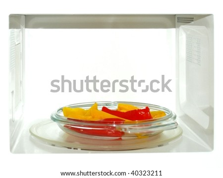 Microwave oven with red and yellow peppers vegetables - stock photo
