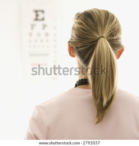 Mid-adult African-American doctor with clipboard and Caucasion mid-adult female patient in doctor's office looking at viewer and smiling.
