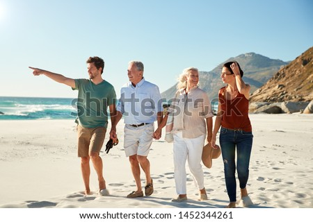 Mid adult and senior white couples walking on a beach together talking, full length, close up