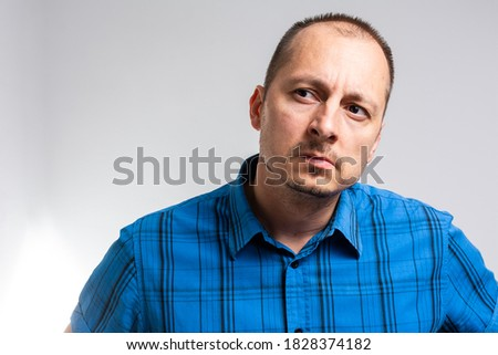 Mid adult attractive male with skeptic look, raises eyebrow in bewilderment, has some doubts and uncertainty, looks curiously aside, isolated over white background with copy space for text Сток-фото ©