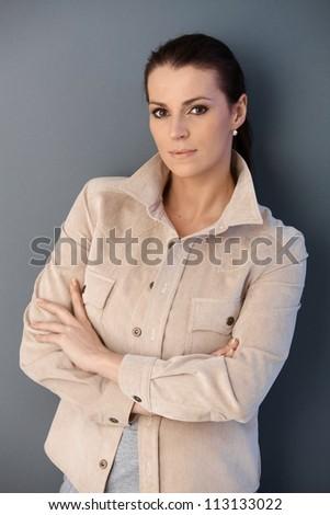 Mid-adult attractive woman posing in studio, grey background.