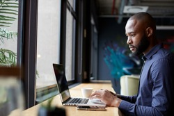 Mid adult black male creative sitting by window in an office social area using a laptop, side view