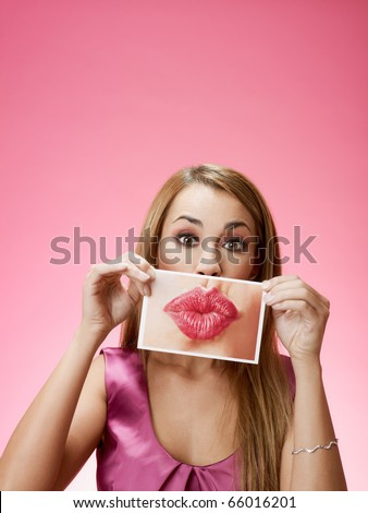 mid adult blond woman holding photo of her mouth kissing on pink background. Horizontal shape, front view, head and shoulders, copy space