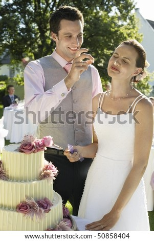 Mid adult bride and groom cutting wedding cake, groom putting bit of cake on bride's nose