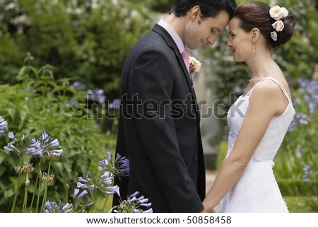 Mid adult bride and groom in garden, face to face, side view