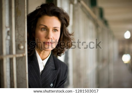 Mid-adult business woman inside a cell of a derelict building Stock photo ©