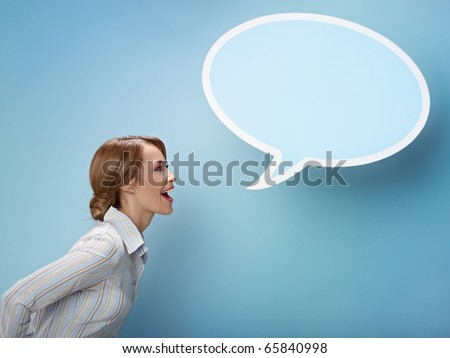mid adult business woman screaming in blank speech bubble on blue background. Horizontal shape, side view, waist up, copy space