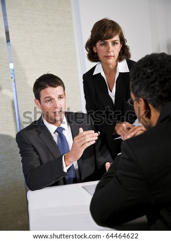 Mid-adult businessman and businesswoman meeting and negotiating with African American man