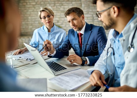 Mid adult businessman and group of doctors working on a computer during a meeting.