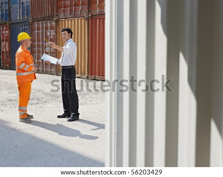 mid adult businessman and manual worker standing near cargo containers. Horizontal shape, full length, copy space