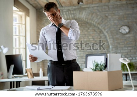 Mid adult businessman feeling worried while reading a notice about his dismissal in the office.