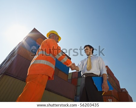 Mid adult businessman holding clipboard and shaking hands to manual worker near cargo containers. Horizontal shape, low angle view. Copy space