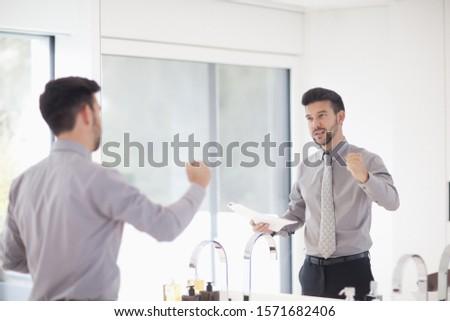 Mid adult businessman practicing presentation in mirror