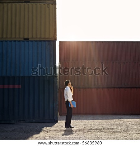 Mid adult businessman standing near cargo container with hand on chin and looking up. Square shape, full length, side view, copy space
