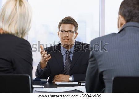 Mid-adult businessman talking to colleagues at office meeting.