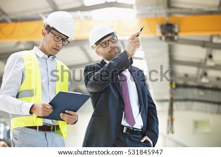 Mid adult businessman with supervisor having discussion in metal industry