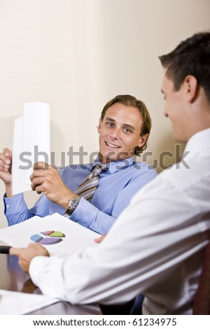 Mid-adult businessmen discussing financial results looking at pie chart