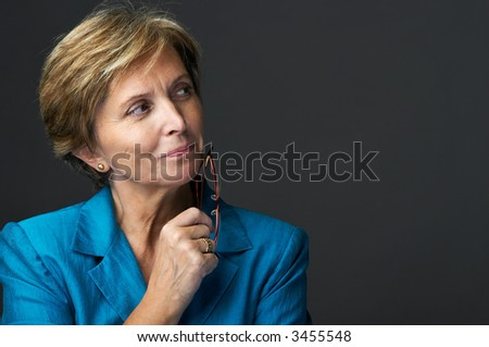 Mid adult businesswoman holding glasses and looking sidewards.