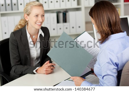 Mid adult businesswoman reading female candidate's CV at office desk