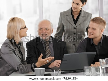 Mid-adult businesswoman talking to team on meeting, gesturing at laptop computer screen, smiling.?