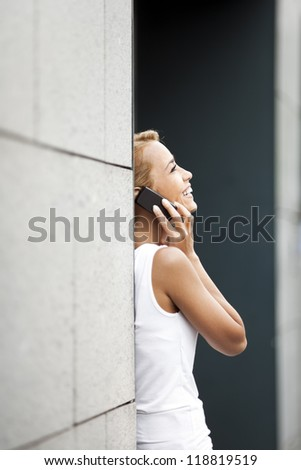 mid adult caucasian business woman talking on mobile phone and leaning on wall near office building. Copy space