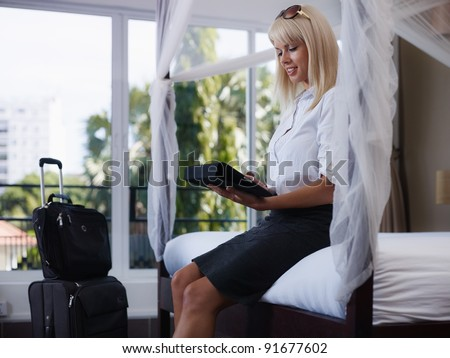Mid adult caucasian businesswoman typing on tablet pc in hotel room during business travel. Side view, three quarter length