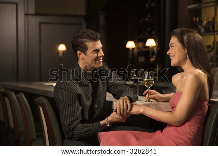 Mid adult Caucasian couple at bar holding hands and smiling.