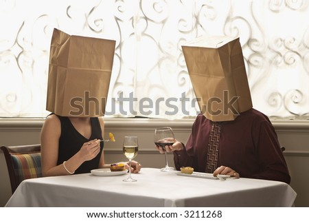 Mid adult Caucasian couple dining in a restaurant with paper bags over heads.