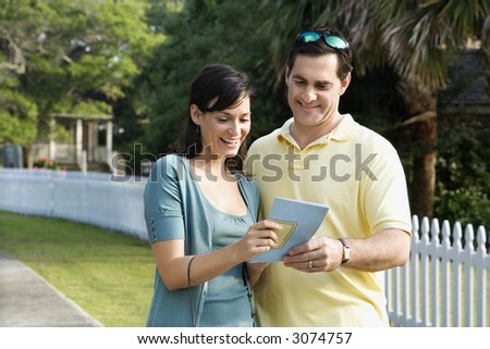 Mid-adult Caucasian couple holding a map and smiling.