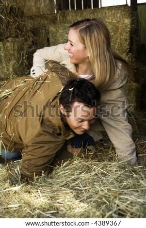 Mid-adult Caucasian couple wrestling in hay.