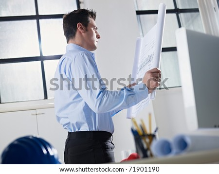 mid adult caucasian male architect examining building plan. Horizontal shape, waist up, side view