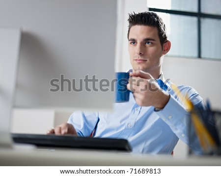 mid adult caucasian male business man looking at computer screen and holding blue coffee cup. Horizontal shape, waist up, front view