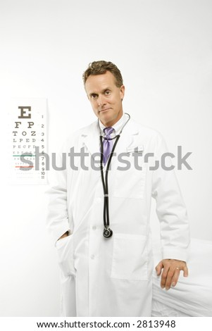 Mid-adult Caucasian male doctor with eye chart in background.