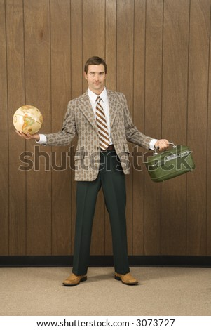 Mid-adult Caucasian male in retro suit holding luggage and a globe. - stock photo