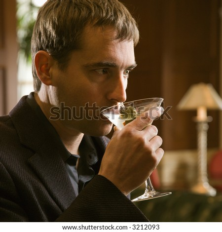 Mid adult Caucasian man drinking martini. - stock photo