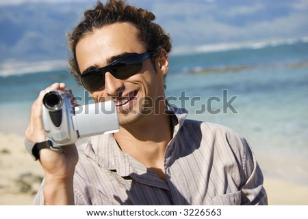 Mid-adult Caucasian man on beach pointing video camera at viewer.