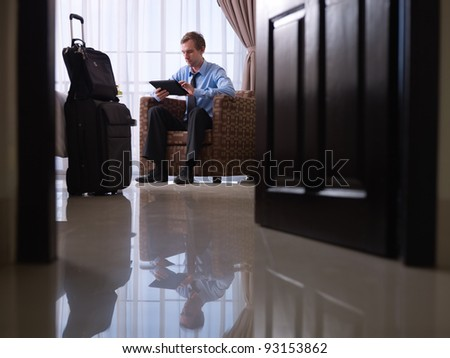 Mid adult caucasian manager typing on tablet pc in hotel room during business travel. Low angle view, full length - stock photo