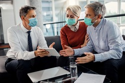 Mid adult couple and their financial advisor using digital tablet while wearing protective face masks during the meeting.