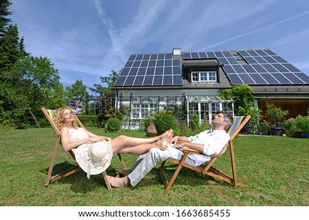 Mid adult couple in deckchairs in garden of solar paneled house