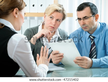 stock photo : mid adult couple meeting with agent or advisor