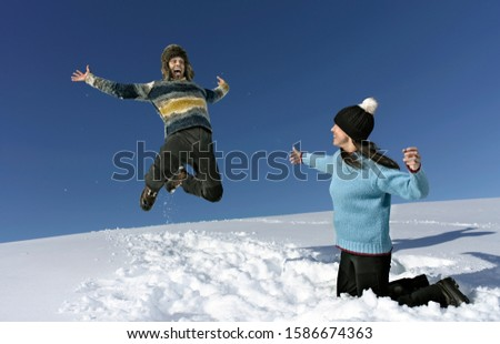 Mid adult couple playing in snow, man jumping in air