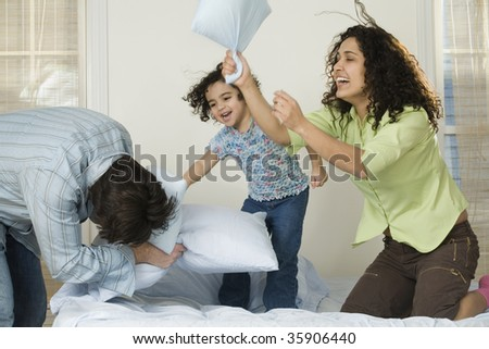 Mid adult couple playing with their daughter