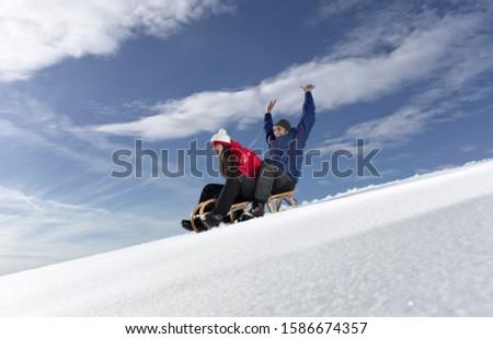 Mid adult couple snow sledding on snow slope