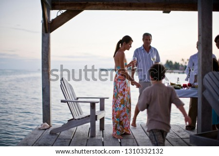 Mid-adult couple standing on a deck with friends.