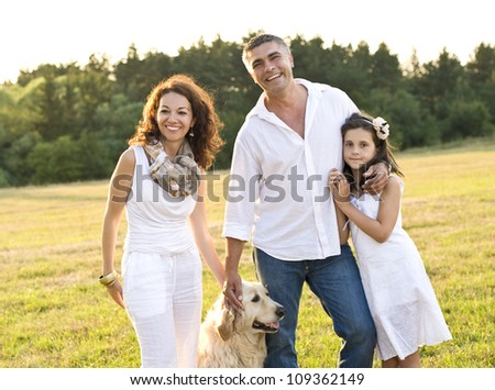 Mid adult couple with daughter and dog in the park