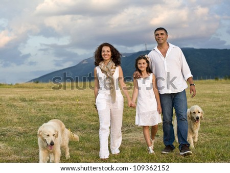 Mid adult couple with daughter and dogs in the park