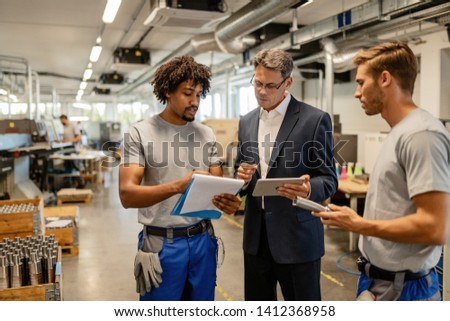 Mid adult engineer and metal workers cooperating while analzying production reports in industrial building.