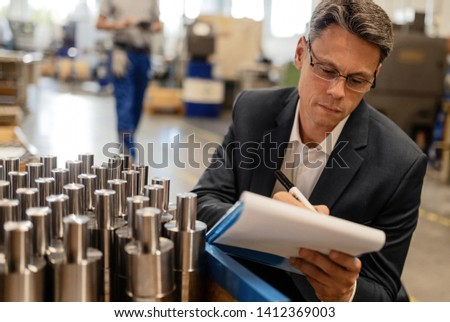 Mid adult engineer taking notes while inspecting steel cylinders in industrial building.