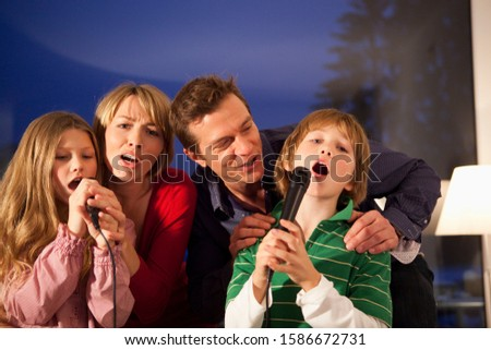 Mid adult family singing karaoke at home